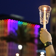 A person holds up a candle in front a rainbow lit building during a vigil at the Dr. Phillips Center for the Performing Arts for the victims of a mass shooting at the Pulse nightclub Monday, June 13, 2016, in Orlando, Florida.  A gunman killed dozens of people in a massacre at the crowded gay nightclub in Orlando on Sunday, making it the deadliest mass shooting in modern U.S. history. (Alex Menendez via AP)