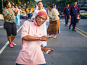 30 OCTOBER 2014 - BANGKOK, THAILAND: A man dances on Chakkaphatdi Phong Street in front of Wat Saket during the parade marking the start of the annual temple fair at Wat Saket. Wat Saket is on a man-made hill in the historic section of Bangkok. The temple has golden spire that is 260 feet high which was the highest point in Bangkok for more than 100 years. The temple construction began in the 1800s in the reign of King Rama III and was completed in the reign of King Rama IV. The annual temple fair is held on the 12th lunar month, for nine days around the November full moon. During the fair a red cloth (reminiscent of a monk's robe) is placed around the Golden Mount while the temple grounds hosts Thai traditional theatre, food stalls and traditional shows.   PHOTO BY JACK KURTZ