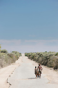 A man and boy with a cart walk along a long, dusty, broken road towards Fort Dauphin, Madagascar