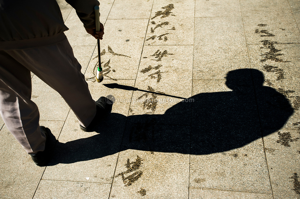 A man practices writing calligraphy on the sidewalk with a large brush soaked in water in Taoranting park in Beijing, China.