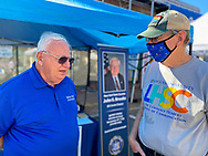 Bellmore, New York, U.S. September 25, 2021. L-R, NYS Senator JOHN BROOKS and visitor BOB STUHMER, wearing a face mask because of COVID-19, chat at the senator's booth the 34th Annual Bellmore Family Street Festival.