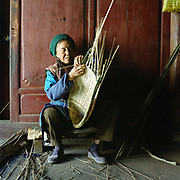 An elderly Bai ethnic minority woman makes a bamboo basket for carrying vegetables in her home, Xizhou, Yunnan Province, China. The People's Republic of China recognises 55 ethnic minority groups in China in addition to the Han majority. The ethnic minorities form 9.44% of mainland China and Taiwan's total population and the greatest number can be found in Yunnan Province, 34% (25 ethnic groups).