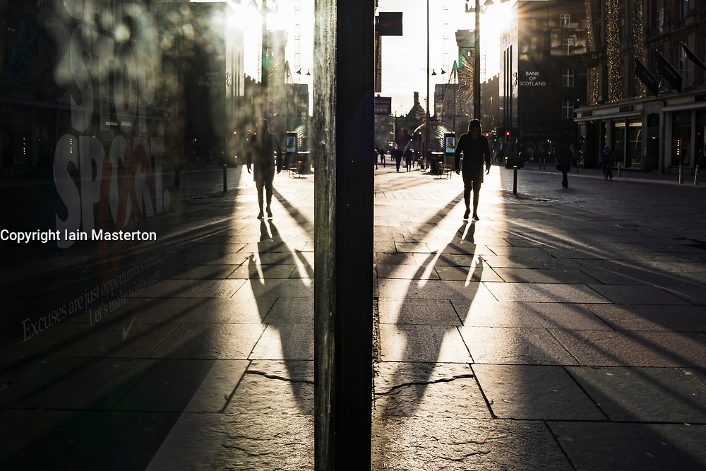 Glasgow, Scotland, UK. 25 November 2020. Glasgow city centre  very quiet during severe level 4 lockdown imposed by the Scottish Government.  Non essential businesses , bars, restaurants and shops are closed. Pictured; Reflection of pedestrian on Buchanan Street. Credit.  Iain Masterton