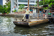 14 NOVEMBER 2012 - BANGKOK, THAILAND: A passenger on a cross khlong ferry that is pulled by operators using ropes and pulleys waits to cross Khlong Saen Saeb in Bangkok. There are only 3 or 4 of the small passenger ferries left on the khlong. Bangkok used to be criss crossed by canals (called Khlongs in Thai) but most have been filled in and paved over. Khlong Saen Saeb is one of the few remaining khlongs in Bangkok with regular passenger boat service. Boats and ships play an important in daily life in Bangkok. Thousands of people commute to work daily on the Chao Phraya Express Boats and fast boats that ply Khlong Saen Saeb. Boats are used to haul commodities through the city to deep water ports for export.      PHOTO BY JACK KURTZ