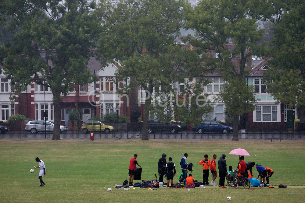 Rain starts falling on a football training session in Ruskin Park, south London. As most players pack their kit away and prepare to leave the field, one last youth player diligently practices his keepie uppies. The park is used widely for organised Saturday and holiday football youth clubs to learn skills and discipline in an area of high youth offences and gang crime. Wealthy homes are seen in the background, properties from the Edwardian era which sell for up to a million Pounds.
