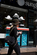 Woman walks past a sunglasses shop featuring three hats suspended from the store window ceiling.