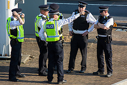 London, UK. 19th April, 2019. Police officers confer alongside the main motorway approach to Heathrow airport. A large policing operation was put in place in and around the airport in preparation for expected protests by climate change activists from Extinction Rebellion. Only a very small symbolic protest by teenage activists from Extinction Rebellion Youth took place, dispersed by police officers under threat of arrest.