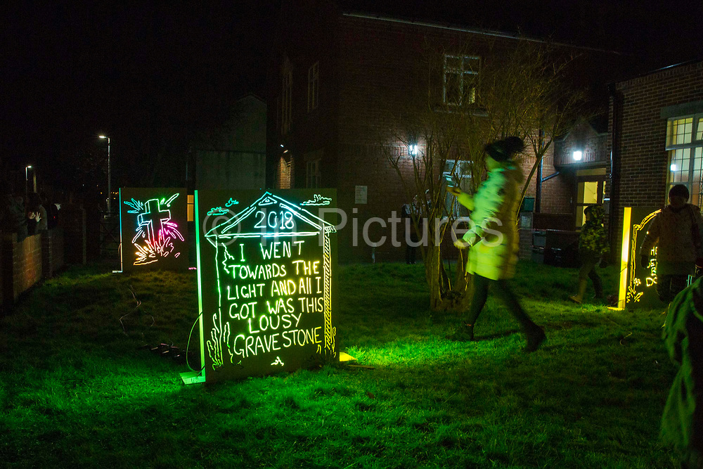 Gravestones. Part of the 'R.I.P It Up & Start Again' installation by Richie Moment as part of the Cheriton Light Festival 2018 in St Andrew's Church Gardens, Folkestone, Kent, United Kingdom. The idea of this exhibition is to show what people want to say once they're dead.