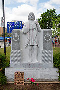 """Wilkes-Barre, PA (July 11, 2020) -- A cardboard sign placed at the Christoper Columbus statue in Wilkes-Barre's Public Square reads """"Columbus: racist, rapist, murderer, slaver."""""""