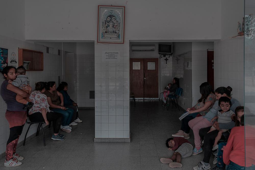 Centro Primario de Salud del pueblo. Las madres con sus hijos aguardan en la sala de espera. El único Hospital de alta complejidad en el que se pueden atender los niños con discapacidades y patologías complejas se encuentra en la Capital de la provincia, a más de 3 horas de viaje. En este pueblo faltan insumos y profesionales para intentar dar respuesta a la alta demanda en salud. Como dato alarmante, existen tres ejes de alto impacto ambiental en esta zona geográfica de Argentina denominada NOA (Noroeste Argentino). Por un lado, la minería a cielo abierto que data desde tiempos prehispánicos, por el otro las fumigaciones de los cultivos con agro tóxicos y, desde hace más de treinta años, se instaló en la región una Curtiembre denunciada por los vecinos y asambleas medio ambientales por verter efluentes altamente contaminantes directamente sobre la tierra y el agua. Entre los mismos se encuentran el cromo, el plomo, ácido sulfúrico y sulfhídrico, amoníaco, cal, entre otros. El agua, la tierra y el aire se encuentran contaminados en esta región y sin embargo son muy pocos los que se atreven a levantar la voz. La vida transcurre bajo intensos calores de montaña, trabajos precarizados en las cosechas del olivo, silencio social y amenazas de toda índole.