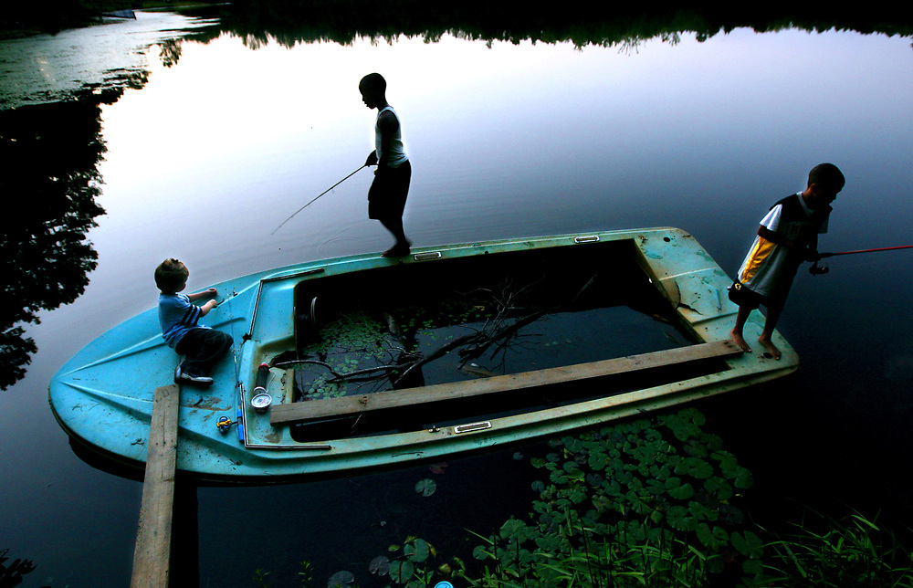"""Hopkins, SC 09-08-07. C. Aluka Berry - The State. /caberry@thestate.com<br /> To some it's just a sunken boat. To 11 year-old Michael """"Little Mike"""" Archie, center, and his friends, William Crawford,6, left, and Mark Dennis,9,  it's the best fishing hole in the world. Only a two minute walk from his house and the fun begins! He borrows hooks, weights and corks, and gets worms any way he can.  Little Mike is on a mission to catch the Big One.  Maybe the biggest one ever at the pond in the Greenlakes subdivison. <br /> <br /> Oh yeah, he's caught some big ones. Some of the best-looking bream in the pond. Double-hand size bream. Bream so pretty it makes the whole neighborhood proud. There's no place Little Mike would rather be than on that water, throwing out his line and waiting... waiting for the next beauty that comes along."""