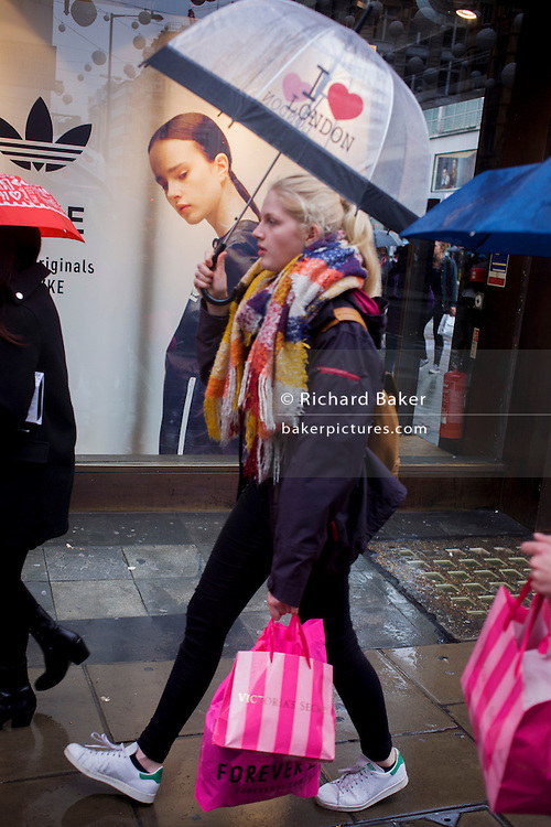 Model on an Adidas seemingly looks over her shoulder to watch young woman passer-by on Oxford Street, London.