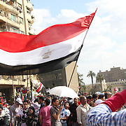 A young man summons all the strength he can muster to wave an enormous Egyptian flag in Cairo's Tahrir Square.