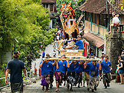 16 JULY 2016 - UBUD, BALI, INDONESIA: Men run up a hill carrying a sarcophagus to the cremation site in Ubud. Local people in Ubud exhumed the remains of family members and burned their remains in a mass cremation ceremony Wednesday. Almost 100 people were cremated and laid to rest in the largest mass cremation in Bali in years this week. Most of the people on Bali are Hindus. Traditional cremations in Bali are very expensive, so communities usually hold one mass cremation approximately every five years. The cremation in Ubud concluded Saturday, with a large community ceremony.     PHOTO BY JACK KURTZ
