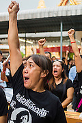 28 APRIL 2014 - BANGKOK, THAILAND:  A woman wearing a tee shirt with Kamol Duangphasuk's photo on it chants his name during the funeral for Kamol at Wat Samian Nari in Bangkok. Kamol was a popular poet who wrote under the pen name Mai Nueng Kor Kunthee. Kamol had been writing since the 1980s and was an outspoken critic of the 2006 coup that deposed Thaksin Shinawatra. After the 2010 military crackdown against the Red Shirts he went into temporary self imposed exile fearing for his safety. After he returned to Thailand he organized weekly protests against Thailand's Lese Majeste laws, which he said were being used to stifle dissent. Kamol was shot and murdered on April 23. The assailants are still at large but the murder is thought to be political.    PHOTO BY JACK KURTZ