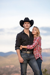 cowboy with a beautiful girl outdoors on a mountain view ranch