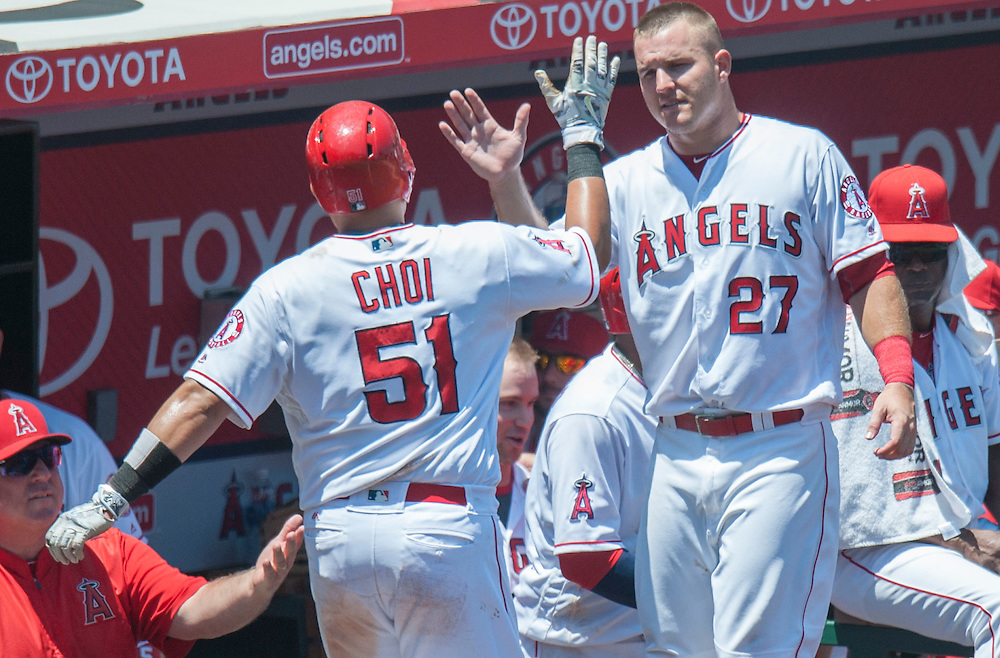 The Angels' Ji-Man Choi is welcomed into the dugout by Mike Trout after scoring on a Jett Bandy double in the fourth inning at Angel Stadium on Sunday.<br /> <br /> ///ADDITIONAL INFO:   <br /> <br /> angels.0718.kjs  ---  Photo by KEVIN SULLIVAN / Orange County Register  -- 7/17/16<br /> <br /> The Los Angeles Angels take on the Chicago White Sox at Angel Stadium.