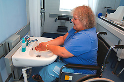 Disabled woman washing her hands in a specially adapted sink for wheelchair users UK