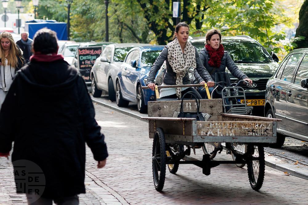 In Utrecht fiets een vrouw met een grote bakfiets over de Oudegracht terwijl een andere vrouw op de fiets haar in wil halen.<br /> <br /> In Utrecht a woman is cycling with a big cargo bike at the Oudegracht while another woman is trying to pass her on the bicycle.