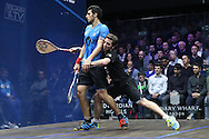 Mathieu Castagnet of France (wearing Black shirt) collides into Omar Mosaad of Egypt (wearing light Blue shirt) in the final .the Final, Omar Mosaad of Egypt v Mathieu Castagnet of France , Canary Wharf Squash Classic 2016 , at the East Wintergarden in Canary Wharf , London on Friday 11th March 2016.<br /> pic by John Patrick Fletcher, Andrew Orchard sports photography.