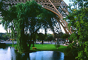 Eiffel Tower Legs with park with blue sky and pond.