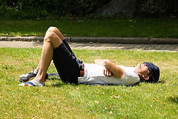 © Licensed to London News Pictures. 24/06/2014. London, UK. A man relaxes on a small green space near Tower Hill during the hot weather in London at lunchtime today. Photo credit : Vickie Flores/LNP