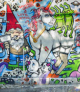 A colorful wall mural in an alley off of Melrose Ave. in Los Angeles, California depicts a gnome with a red hat, a unicorn with space aliens on its back, a spaceship, and other stylized creatures