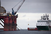 Greenpeace activists board a BP oil rig in Cromarty Firth to stop it from further oil drilling at sea, June 10th 2019, Cromarty, Scotland, United Kingdom. The oil rig Paul B. Loyd, Jnr, owned by Transocean, was due to head to BPs Vorlich field, 150 miles 241km east of Aberdeen to drill for oil for BP. Oil rig crew comes off the rig by crane. The occupation by Greenpeace activists subsequently delayed the departure for 5 days and 14 activists were arrested in the process. Greenpeace says that in an age of climate emergency BP should not be drilling for new oil but look for non-fossil fuel means of energy.