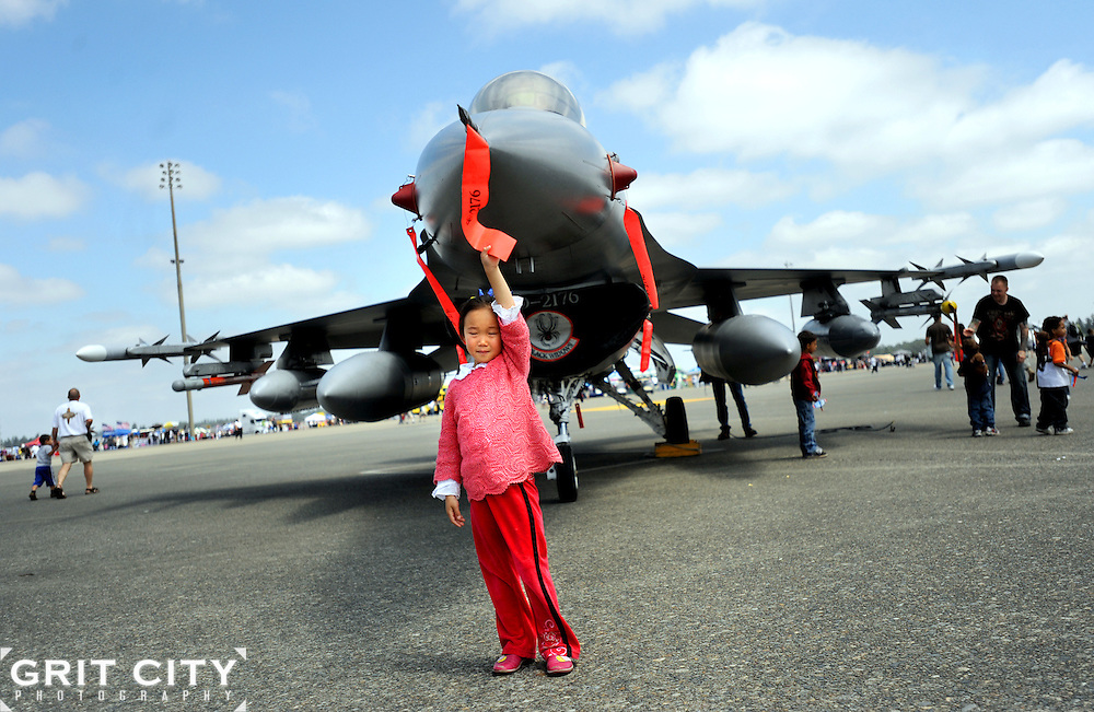 A young girl poses for a photo in front of a jet on display at Saturday's JBLM Air Expo.