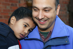 Young boy resting his head on his father's shoulder,