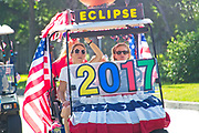 A family rides a golf cart celebrating the upcoming solar eclipse during the annual Sullivan's Island Independence Day parade July 4, 2017 in Sullivan's Island, South Carolina. The solar eclipse will be visible from the Charleston area for the longest period in the continental USA before moving over the Atlantic Ocean.