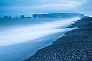 """Dyrhólaey on the southcoast of Island is a 120 meter high peninsular, mostly consisting of vulcanic tuff. """"Dyr"""" is Icelandic for door, and the name Dyrhólaey comes from a characteristic door in the rock, which you can see at the top in the picture. This picture is long exposed - hence the soft look of the sea   Dyrhólaey på sørkysten av Island, er en ca. 120 meter høy halvøy og består for det meste av vulkansk tuff. """"Dyr"""" er Islandsk for dør, og navnet Dyrhólaey kommer av en karakteristisk dør i berget. Du ser et hol i berget i toppen av bildet. Bildet er tatt med lang lukketid, derav de silkemyke utseende i sjøen."""