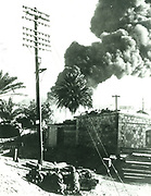 Suez Crisis or Tripartite Agression, 1956. French parachutists in action against Egyptian forces at Port Said.  A fuel dump is burning in the background.