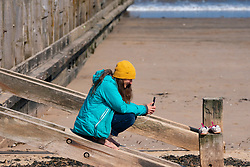 Portobello, Scotland, UK. 25 April 2020. Views of people outdoors on Saturday afternoon on the beach and promenade at Portobello, Edinburgh. Good weather has brought more people outdoors walking and cycling. Police are patrolling in vehicles but not stopping because most people seem to be observing social distancing. Woman sitting on wooden groyne.  Iain Masterton/Alamy Live News