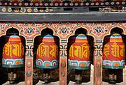 A row of four brightly painted prayer wheels at the state monastic school Dechen Phodrung Monastery. Thimpu, Druk Yul, Bhutan. 13 November 2007