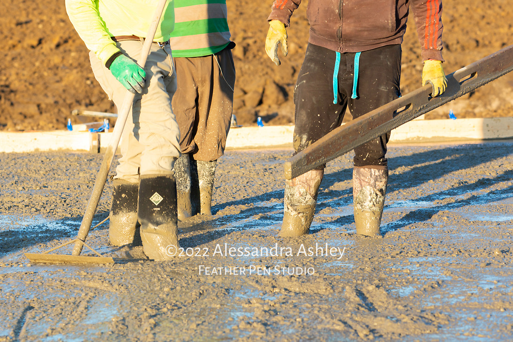 Building crew with boots in wet cement during slab pouring process for new physical therapy and wellness center construction project. Athletic Advantage, Lewis Center, Ohio.