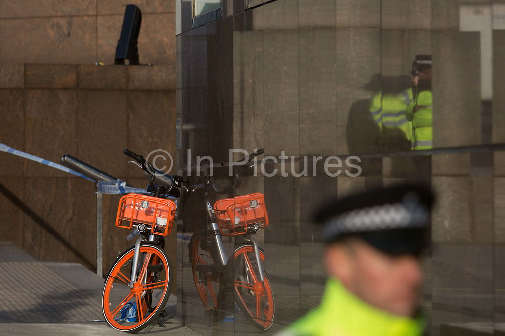 The morning after the terrorist attack at Fishmongers Hall on London Bridge, in which Usman Khan a convicted, freed terrorist killed 2 during a knife a attack, then subsequently tackled by passers-by and shot by armed police - officers guard the southern end of the bridge where a rental bike has been abandoned during the evacuation, on 30th November 2019, in London, England.