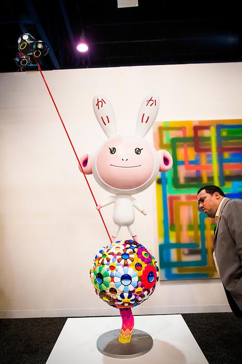 An art-lover studies Kaikai Kiki, a  fiberglass sculpture by Takaashi Murakami, at the Paris- and Miami-based Galerie Emmanuel Perrotin's space at Art Basel Miami Beach 2007
