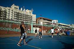 © London News Pictures. 23/09/2013 . Brighton, UK.   A group of men take part in a game of basketball in bright sunlight on Brighton seafront in front of The Brighton Centre where the Labour Party Conference is currently taking place. . Photo credit : Ben Cawthra/LNP