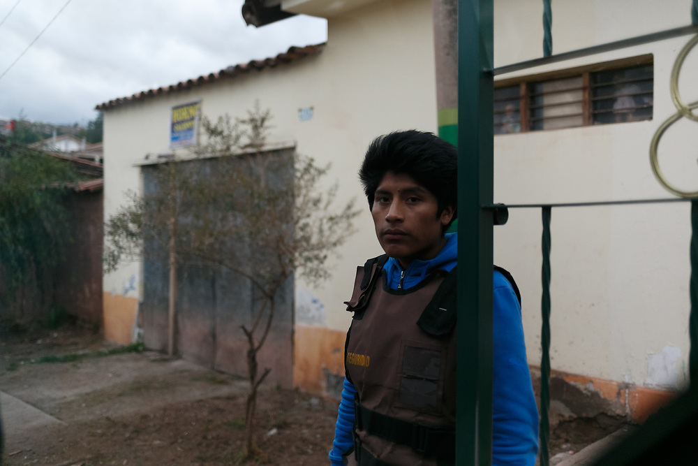 Security guard mans an entrance to a gated community in Cusco, Peru. Photography by Chris Aluka Berry.