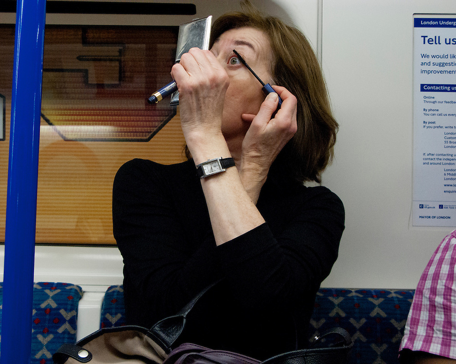 Portrait of a Female Londoner travelling on the Underground Network applying make-up