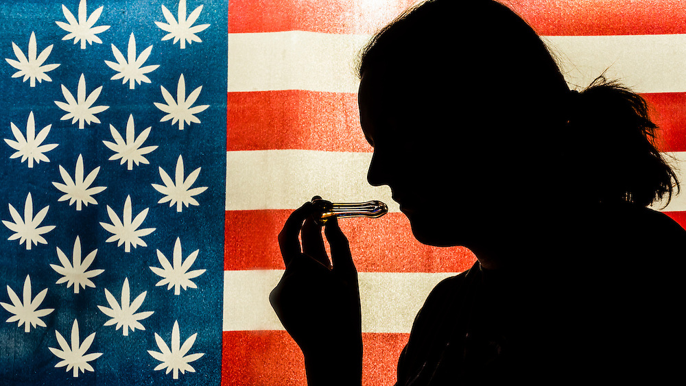 Man smoking a pipe with American marijuana flag in background, Littleton, Colorado USA.  Colorado was the first state to legalize the sale of marijuana for recreational use in 2014.