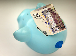 File photo dated 06/01/15 of money in a piggy bank. Hard-pressed households need stronger action to help them deal with debts and save for a rainy day and a pension, MPs have urged.