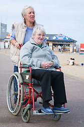 Carer pushing a wheelchair user along on a sea front path during a day trip to Skegness organised by Nottingham Disabled Friendship Club,