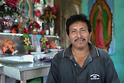 """Frejedes Catch, 41, from Xaibé, smiles in front of an altar for the Virgin of Guadalupe in his living room. Mr. Catch, who has been growing sugar cane for 26 years, declares: """"Fairtrade has helped us a lot. It has provided monetary aid for our children who study. Also, the Fairtrade standards have helped improve our environment as less people have been intoxicated by following the improved storage regulations. Also, there is less plastic on the sugar cane fields. Many of us were not conscious of the secondary problems caused by pollution."""" Belize Sugar Cane Farmers Association (BSCFA), Xaibé, Corozal, Belize. January 22, 2013."""