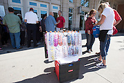 Vendors sell pins and t-shirts to visitors waiting in line to hear presidential candidate Donald Trump speak during a rally at the American Airlines Center in Dallas, Texas on September 14, 2015. (Cooper Neill for The New York Times)