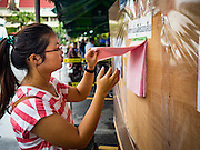 07 AUGUST 2016 - BANGKOK, THAILAND:  A woman looks for her name on voting rolls at a polling place at Wat That Thong in Bangkok. Thais voted Sunday in the referendum to approve a new charter (constitution) for Thailand. The new charter was written by a government appointed panel after the military coup that deposed the elected civilian government in May, 2014. The charter referendum is the first country wide election since the coup.       PHOTO BY JACK KURTZ