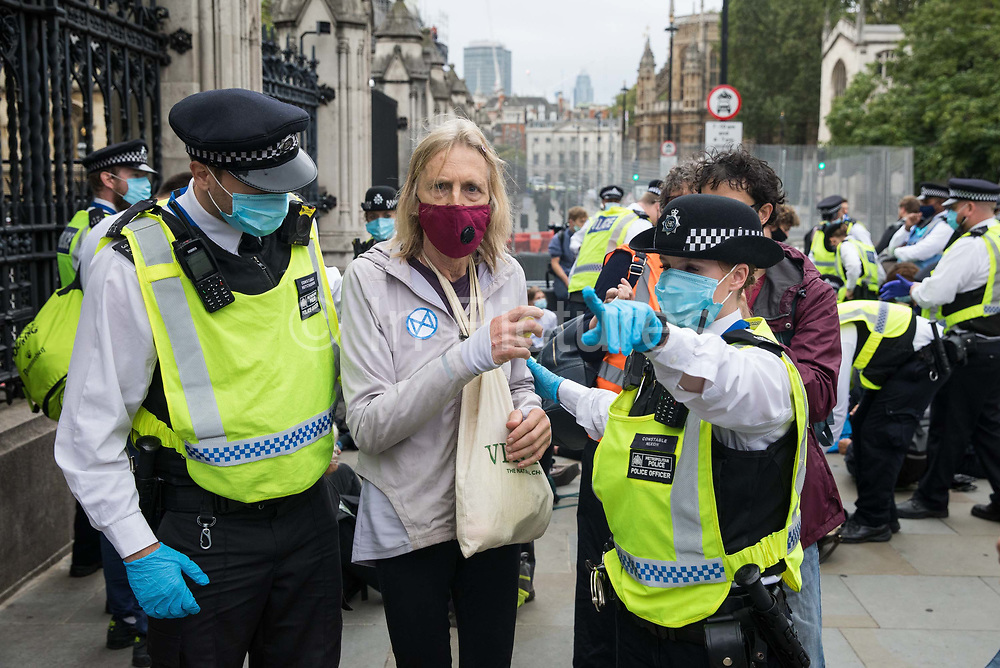 Metropolitan Police officers detain a climate activist from Extinction Rebellion who had occupied the pavement outside the Houses of Parliament on 3 September 2020 in London, United Kingdom. Extinction Rebellion activists are attending a series of September Rebellion protests around the UK to call on politicians to back the Climate and Ecological Emergency Bill CEE Bill which requires, among other measures, a serious plan to deal with the UK's share of emissions and to halt critical rises in global temperatures and for ordinary people to be involved in future environmental planning by means of a Citizens' Assembly.