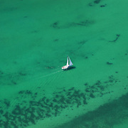 An aerial view of a yacht sailing in the pristine water of the Bay of Islands, North Island, New Zealand. .The Bay of Islands boasts a unique coastline sheltering over 150 small islands in its arms. Once a seafaring and whaling region the Bay of Islands is today a popular tourist destination recognised for it's cultural heritage as well as it's amazing scenery and wildlife. Small towns are scattered along the coastline. There are a lot of water-based activities, including kayaking, swimming with dolphins, game fishing and boating and whales and dolphins can often be seen in the bay. Bay of Islands, New Zealand, 16th November 2010. Photo Tim Clayton.