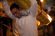 A pilgrim carries an enormous devotional candle to the church of Sant' Alfio during the festival of Sant' Alfio at Trecastagni, Sicily, Italy.